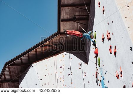 Difficult Tricks. Young Man Professional Rock Climber Practicing At Training Center In Sunny Day, Ou