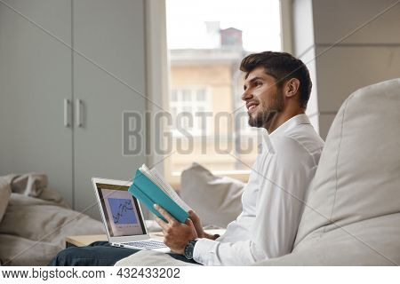 Young thoughtful european businessman reading book and holding laptop computer with business graph. Concept of modern successful man. Bearded stylish guy wears formal clothes. Office interior. Daytime