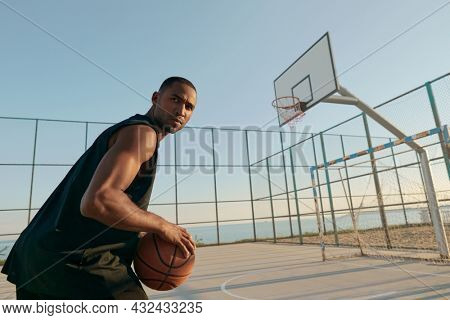Young focused african sportsman holding basketball ball and looking away on sports court. Black man wearing sportswear. Urban basketball player. Sea behind mesh fence. Sunny daytime