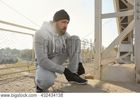 European runner tie shoelaces on sneakers. Young sportsman wear hat, hooded zipper sweatshirt, mittens and sneakers. Man prepare to sport run competition. Person located on iron bridge. Sunny daytime