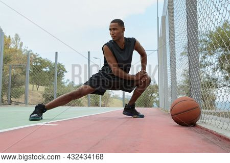 Young african sportsman stretching before training on sport court. Low angle view of black man with towel wear sportswear and sneakers. Urban basketball player. Cloudy day