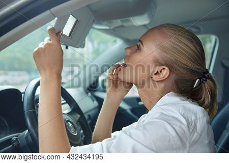 European business woman looking at herself in mirror of personal automobile. Young pretty serious blonde woman wear formal clothes. Idea of mobility. Concept of modern successful woman. Car interior