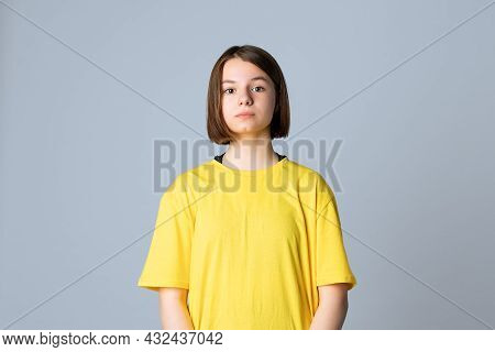 Portrait Of Beautiful Cute Teen Girl In Yellow Casual Tshirt Looking At Camera, Standing Over Light