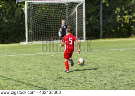 Children Play Football On A Green Field. Motion Effect. Children In A Red Team Play Against Children