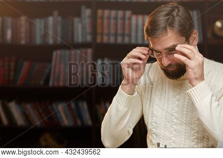 A Thoughtful, Concerned Male Writer Working On A Novel On A Typewriter, Drinking Alcohol While Think