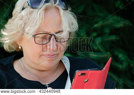 Adult Caucasian Woman With Glasses Intently Reads Information On Phone With Red Cover. Blond Middle