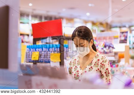Female In Protective Mask Choosing New Books In Book Shop