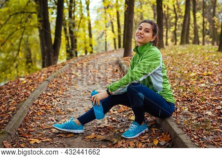 Runner Having Rest After Workout In Autumn Park. Happy Woman Holding Water Bottle Sitting On Path. S