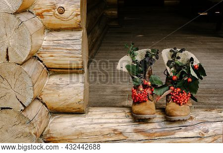Tracking Boots With Autumn Berries And Leaves Standing On The Porch Of A Country House.