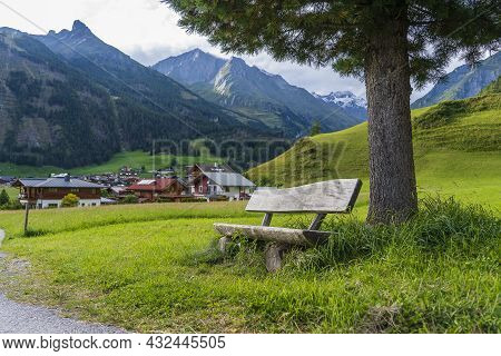 Old Wooden Bench Under A Pine Tree In A Mountain Village At Summer Day In Alps Austria