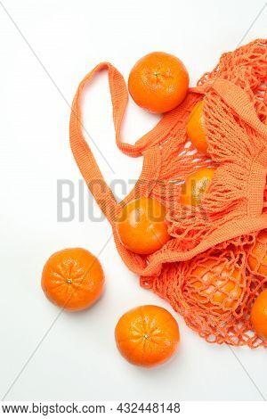 String Bag With Mandarins On White Background