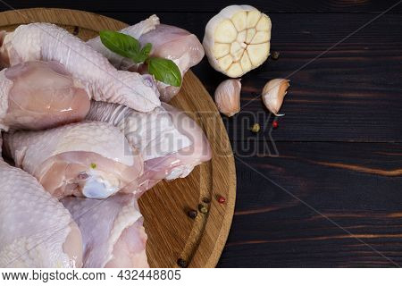 Raw Chicken Legs, Chicken Drumsticks On A Wooden Background With Spices. Copy Space Top View.