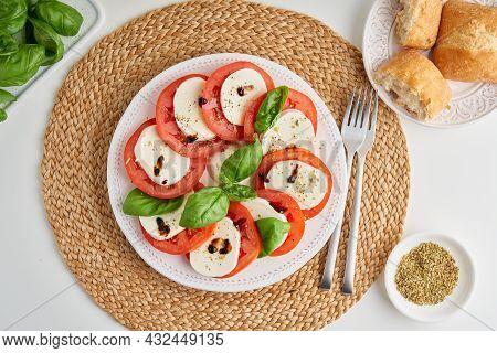 Horizontal Top View Of Classic Italian Caprese Salad With Sliced Tomatoes, Mozzarella, Basil Herb, P
