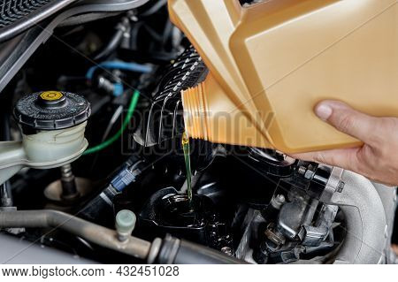 A Man Pouring Oil To Car Engine. Fresh Oil Poured During An Oil Change To A Car Adding Engine Oil In