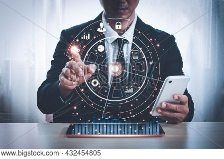 Asian Man In A Suit Is Sitting At A Desk With His Left Hand Holding A Mobile Phone. His Right Hand P
