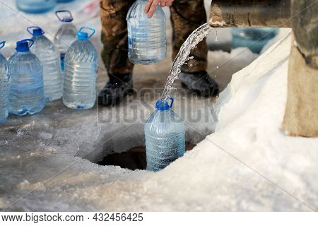 A Man Draws Water From An Icy Drinking Spring. There Are A Lot Of Plastic Containers With Collected