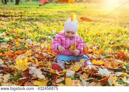 Happy Young Girl Playing Under Falling Yellow Leaves In Beautiful Autumn Park On Nature Walks Outdoo