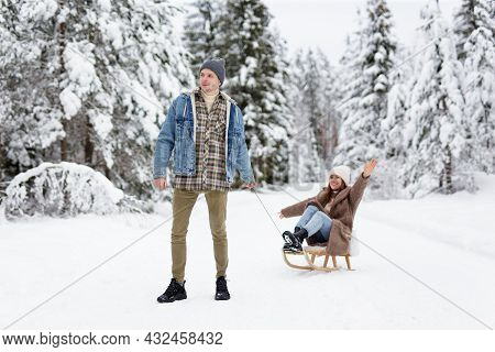 Man Pulling Sledge With His Joyful Girlfriend On Winter Day In Forest
