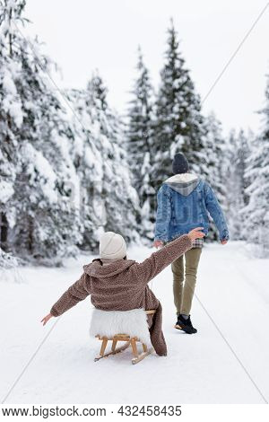 Back View Of  Man Pulling Sledge With His Girlfriend In Winter Forest Or Park