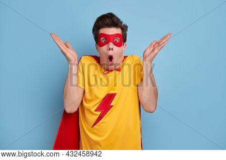 Funny Perplexed Young Male In Superhero Outfit And Mask Shrugging And Looking At Camera With Shock A