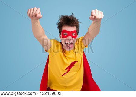 Mad Young Guy In Superhero Costume And Mask Showing Tongue And Raising Fists While Pretending To Fly