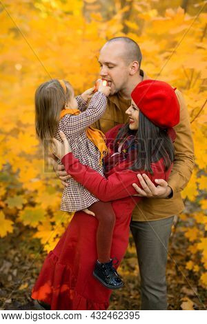 A Child Feeds His Father An Apple, Sitting In His Mother's Arms And Laughing Merrily Against The Bac