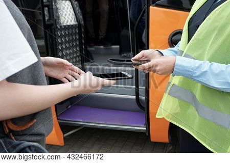 Close-up of unrecognizable supervisor in green vest using phone camera while scanning electronic bus ticket of passenger