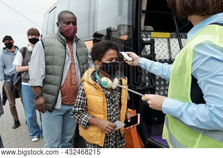 Bus supervisor or conductor using infrared thermometer while checking temperature of black boy before bus boarded