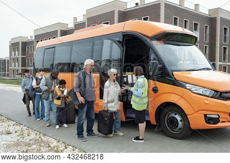 Female transportation supervisor in green vest standing at open bus door and checking tickets of passengers