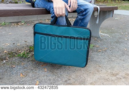 A Schoolboy Sitting In A Park And Waiting For Beginning Of Additional Education Lesson With A Bag Wi