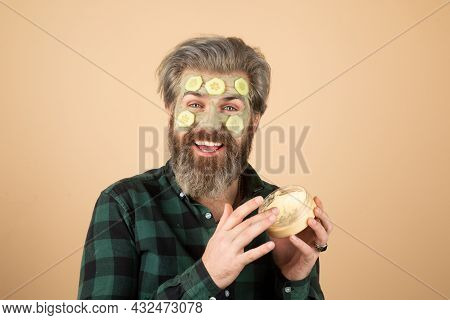 Funny Male Model With Mask And Cucumber Slices On Face. Spa, Dermatology, Wellness And Facial Treatm