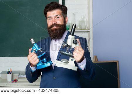 Portrait Of Teacher Man With Microscope, Professor, Tutor, Mentor In School Classroom.