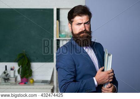 Portrait Of Teacher In Classroom. Handsome Bearded Man Near Blackboard In Classroom. Teacher Profess