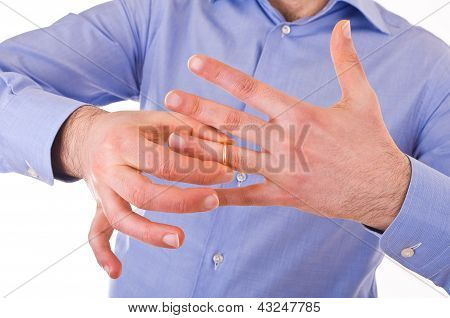 Man taking off his golden wedding ring.