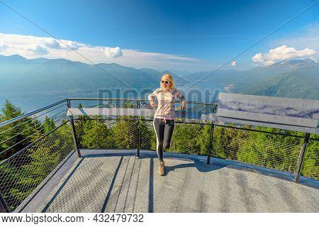 Woman On Aussichtsplattform Cardada Platform On Top Of Cardada-cimetta Mount In Switzerland. Skyline
