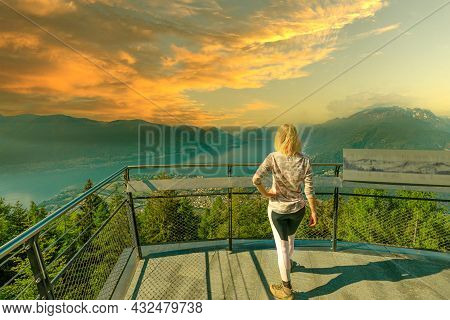 Woman At Sunset On Top Of Cardada-cimetta Mount In Switzerland. Skyline From Swiss Cable Car Of Loca