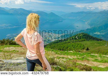Woman Trekking On Top Of Cardada-cimetta Mount In Switzerland. Skyline Of Swiss Cable Car Of Locarno