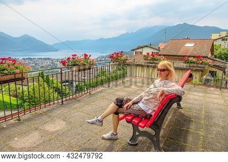 Woman Sitting On Top Of Lake Maggiore In Switzerland. Swiss Bench At Aerial View Lookout From Orseli
