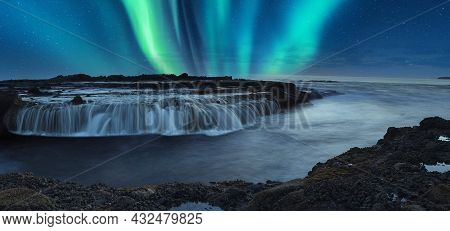 Green Aurora Borealis Shimmers Over The Ocean Water As It Cascades Over Rocks In Reykjavik, Iceland.