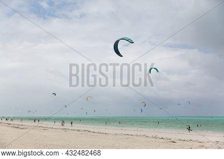 Zanzibar, Tanzania, January 22, 2021: Surfer Beach, Turquoise Sea, Many People Ride Surfboards And K