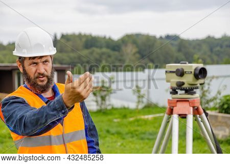 A Civil Engineer With An Optical Level Waves His Hand To Control Colleagues From A Distance.