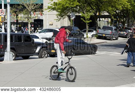 Bronx, New York, Usa - May 20, 2020: Black Male Rides Bicycle While Wearing Mask And Looking At Cel