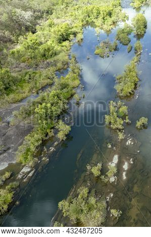 Drone Aerial Landscape Of Shallow Riverbed Pattern With Water Reflections And Shrubs