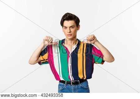 Confident And Sassy Gay Man Pointing At Himself, Looking Self-assured, Standing Over White Backgroun