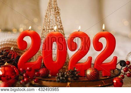Happy New Years 2022. Numbers Of Year 2022 Made By Red Candles On Bokeh Festive Sparkling Background