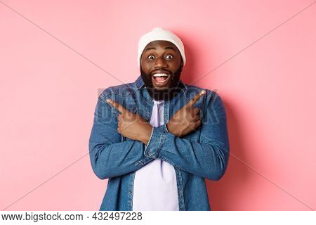 Happy Young African-american Hipster Guy Pointing Fingers Sideways, Smiling And Showing Two Choices,