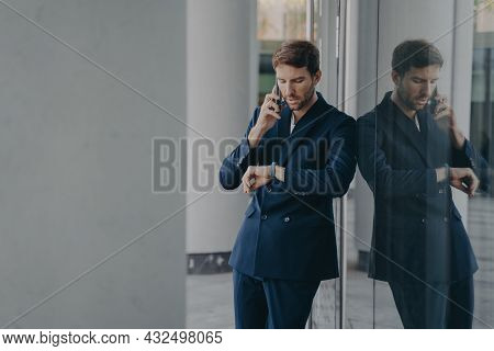 Pensive Young Businessman In Formal Suit Talking On Mobile Phone Standing Outside Of Office Center E