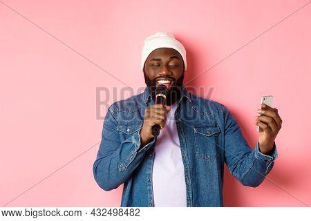 Handsome African-american Man Singing Karaoke, Reading Lyrics On Smartphone App And Holding Micropho