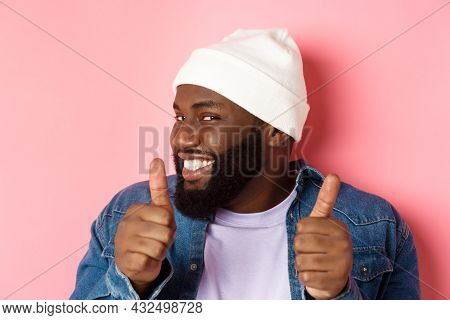 Close-up Of Happy Black Bearded Guy In Beanie Showing Support, Agree Or Approve Something, Giggle De