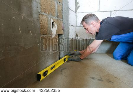 A Male Worker Checks The Evenness Of The Floor And Walls Before Repairing, Using A Building Level. T